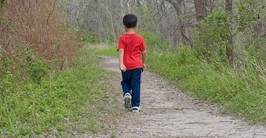 Young child walking alone on a path in the woods.