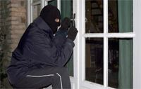 Masked individual attempting a break-in at a home.