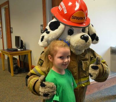 Sparky the Firedog hugging kids at Storytime