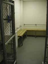 Door leading into jail holding area containing benches.