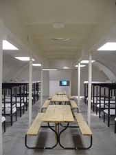 Long-view of jail pod interior containing tables and beds.