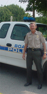 Animal Control Officer Ricky Burke standing next to patrol vehicle.